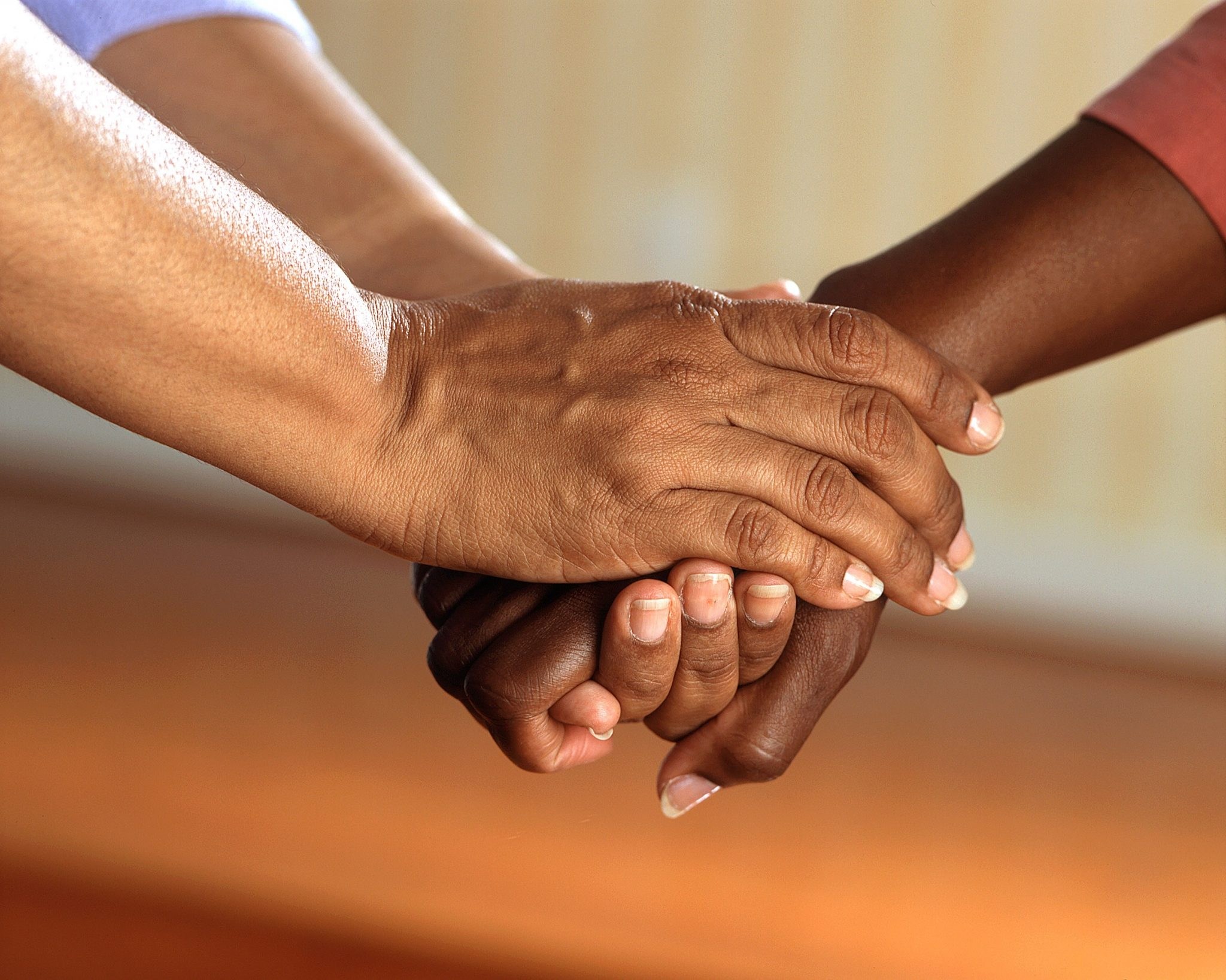 Closeup of three, intertwined hands, meant to represent the bond of a suicide support group