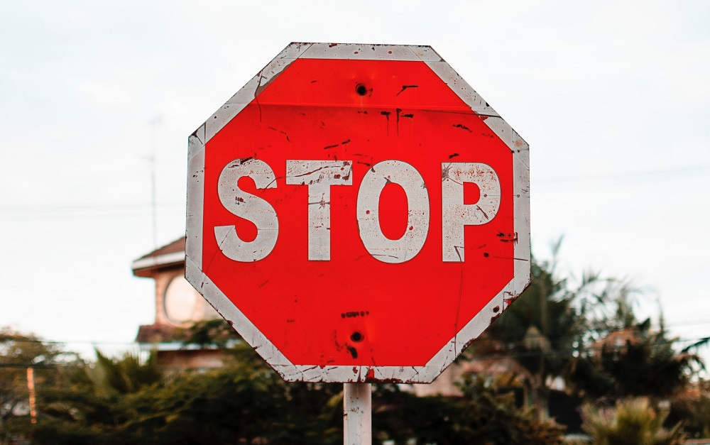 Closeup of a bright red, beat up stop sign with the sky and palm trees in the back, meant to represent the movement to stop mental illness stigma.
