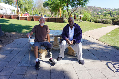 Two older veterans, one with a prosthetic leg, sit in the shade at a picnic bench, looking at the camera.