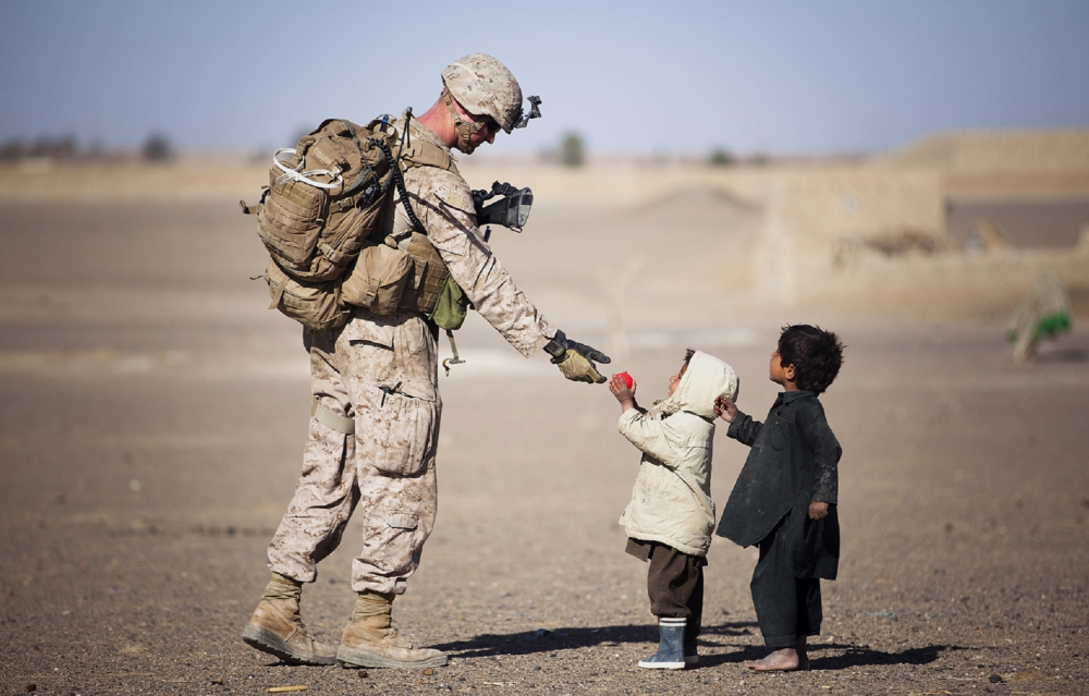 A soldier overseas in the desert, interacting warmly with two local toddlers. The photo is meant to represent the potential effects of moral injury.