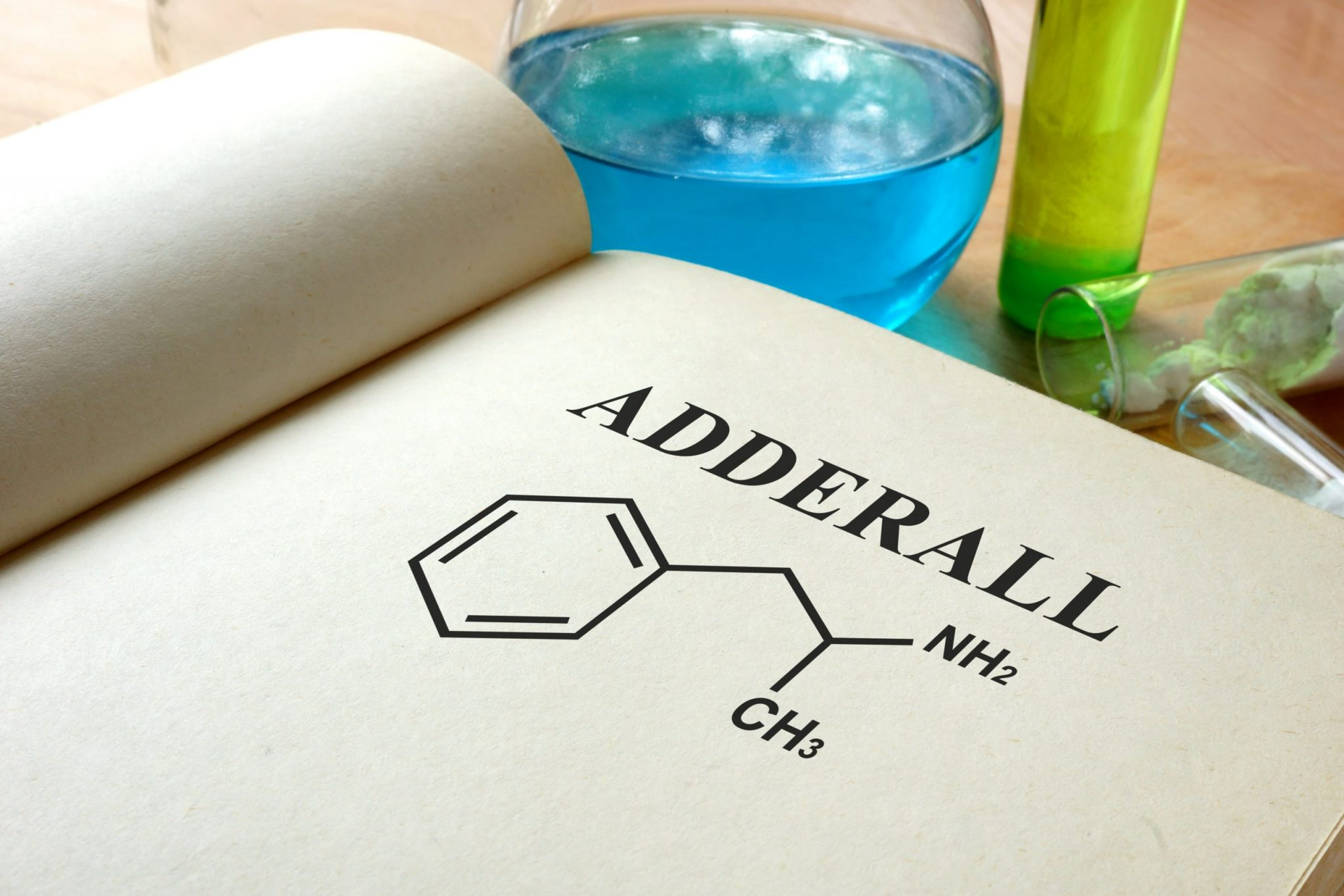 "Book open to the word ""ADDERALL"" written over an illustration of the chemical makeup of the drug. Test tubes and a flask are partially visible in the background."