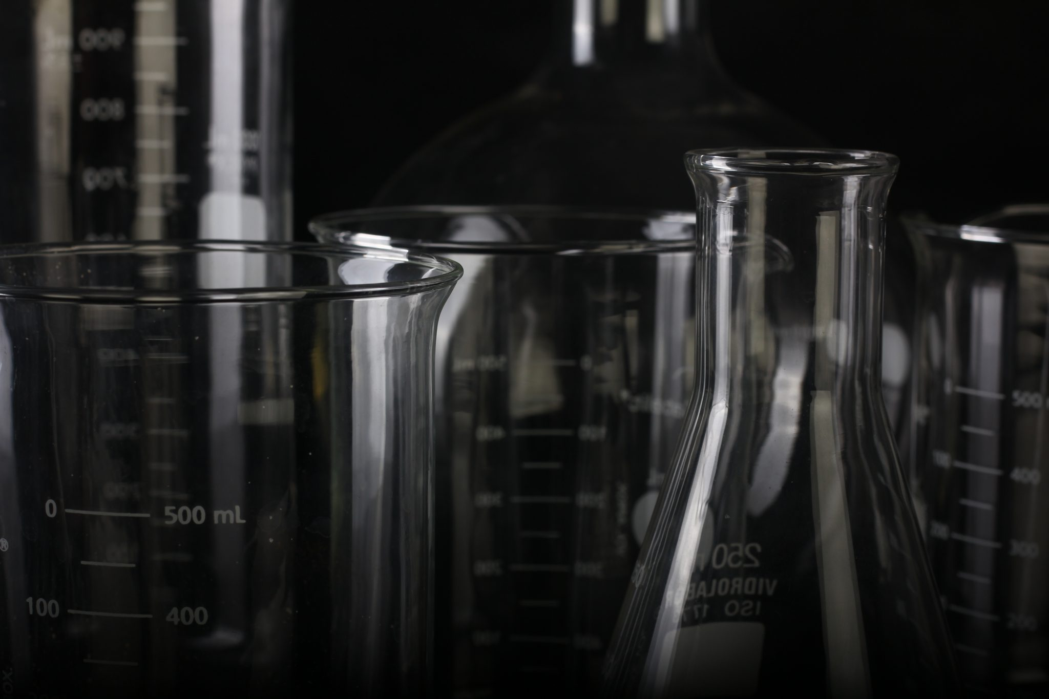 Scientific glass flasks and beakers of various sized against a black background, symbolizing the opioid fentanyl overdose crisis.